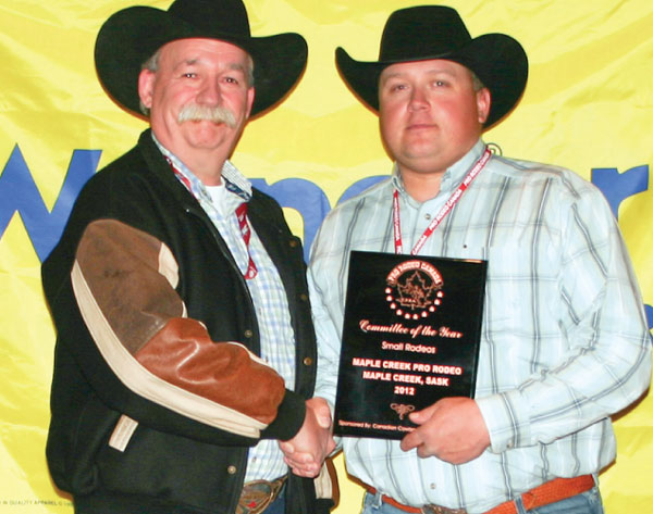 Slim Needham, on behalf of the Maple Creek rodeo committee, accepts the rodeo Committee of the Year Award (Small Rodeo) from sponsor representative Rob Tanner of Canadian Cowboy Country