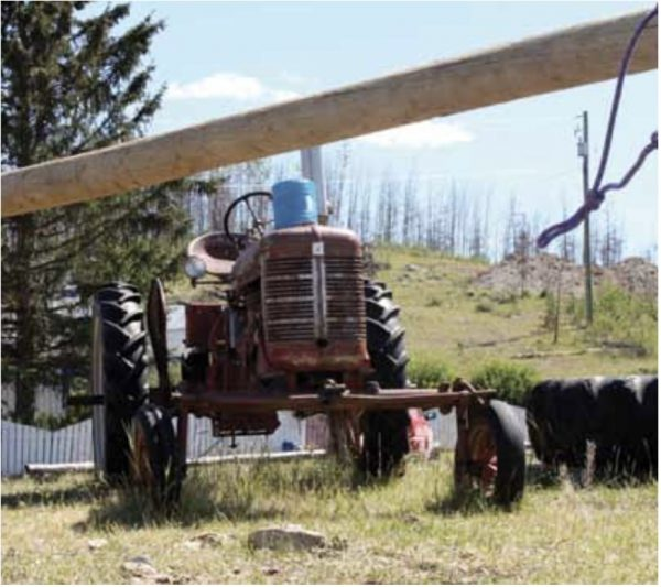 The fire-blackened dead timber on the hill behind the old tractor shows just how close the 2009 forest fire came to the ranch house and buildings